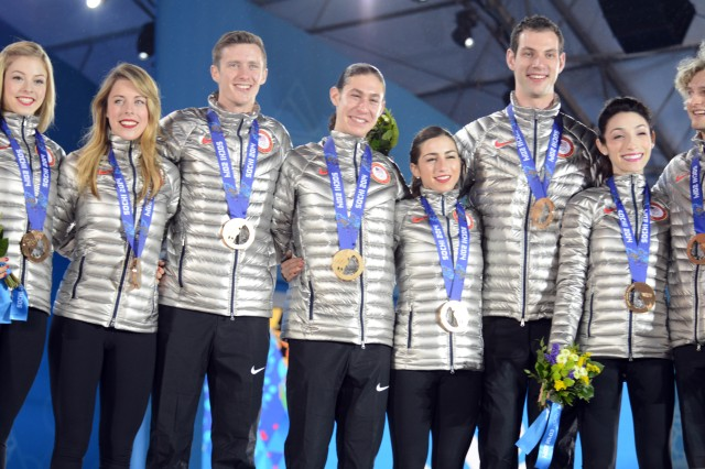 The eight members of Team USA who took bronze in the first-ever Olympic team figure-skating competition stand on stage in Victory Plaza at end of the awards ceremony, Feb. 10, 2014, in Sochi, Russia. Army family member Ashley Wagner stands second from left.