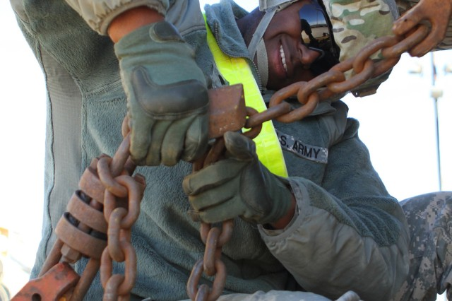 Spc. Andrew Dixon, a fire direction specialist with Battery A, 2nd Battalion, 20th Field Artillery Regiment, Task Force Pegasus Fires, connects the chains used to tie down vehicles to a flat train car at the rail yard on Fort Hood, Texas, Jan. 30. The battalion is preparing vehicles for shipment to the National Training Center at Fort Irwin, Calif. (U.S. Army photo by Sgt. Garett Hernandez, Task Force Pegasus Fires Public Affairs).