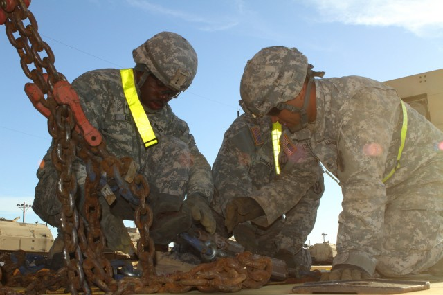 Soldiers from 2nd Battalion, 20th Field Artillery Regiment, Task Force Pegasus, use chains to tie down a multiple launch rocket system to a flat train car at the Fort Hood rail head, Jan. 30. The battalion is preparing vehicles for shipment to the National Training Center at Fort Irwin, Calif. (U.S. Army photo by Sgt. Garett Hernandez, Task Force Pegasus Fires Public Affairs).