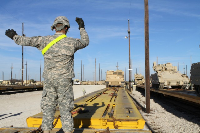 Sgt. John Minteer, a multiple launch rocket system crew member with Battery B, 2nd Battalion, 20th Field Artillery Regiment, Task Force Pegasus Fires, guides an MLRS onto a flat train car at the Fort Hood railhead, Jan. 30. The battalion is preparing vehicles for shipment to the National Training Center at Fort Irwin, Calif. (U.S. Army photo by Sgt. Garett Hernandez, Task Force Pegasus Fires Public Affairs).