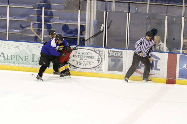 A Soldier and Airman from Fort Wainwright and Eielson Air Force Base fight for the puck during a practice game during Hockey Week at the Dipper Ice Arena in Fairbanks, AK. There will be another game at the University of Fairbanks 28 Feb for the Commander's Trophy.