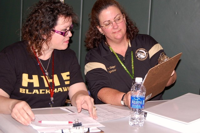 Odette Hatch and Carol Chipps go over names of children who will be arriving at MP Hill Fitness Center, Jan. 30, as part of the Humphreys Middle/High School lockdown and evacuation exercise.