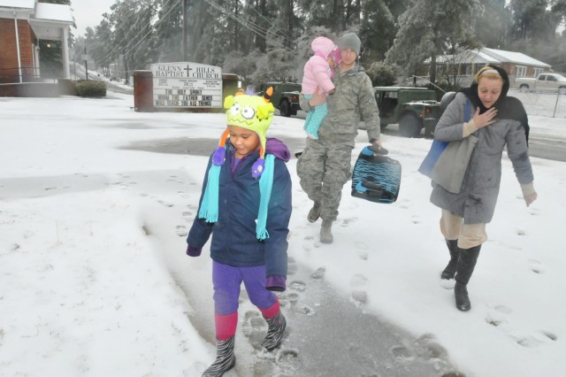 Staff Sgt. Matthew Wainwright, of Savannah's 165th Airlift Wing, Georgia Air National Guard, carries 21-month old Parris into a shelter at the Glenn Hills (Ga.,) Baptist Church during a mission to evacuate a family from their home which lost power and heat during Winter Storm Pax.