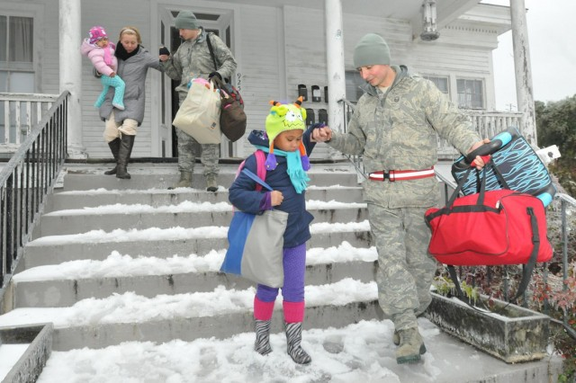 Master Sgt. Jorge Chavez (right) and Staff Sgt. Matthew Wainwright, both with the 165th Airlift Wing, Georgia Air National Guard, help a family evacuate from their home after it lost power and heat during Winter Storm Pax. The guardsmen transported the family to a local church where they will shelter for the duration of the storm.