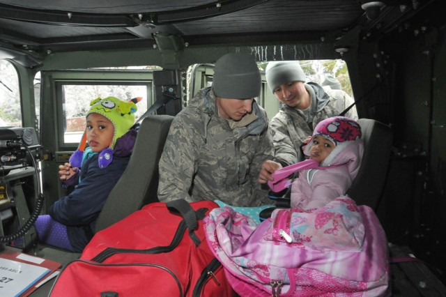 Staff Sgt. Matthew Wainwright (left) and Master Sgt. Jorge Chavez, both of Savannah's 165th Airlift Wing, Georgia Air National Guard, secure 4-month-old Dakota into a Humvee during a mission to evacuate her family from their home which lost power and heat during Winter Storm Pax. The guardsmen transported the family to a local church where they will shelter for the duration of the storm.