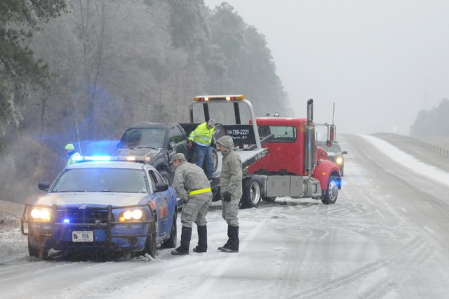 Georgia Guardsman Maj. Nicholas Anthony, Bravo Flight commander, 165th Air Support Operations Squadron, speaks with a Georgia State Patrol officer at the scene of recovery of a vehicle that slid off the road along Interstate 20.