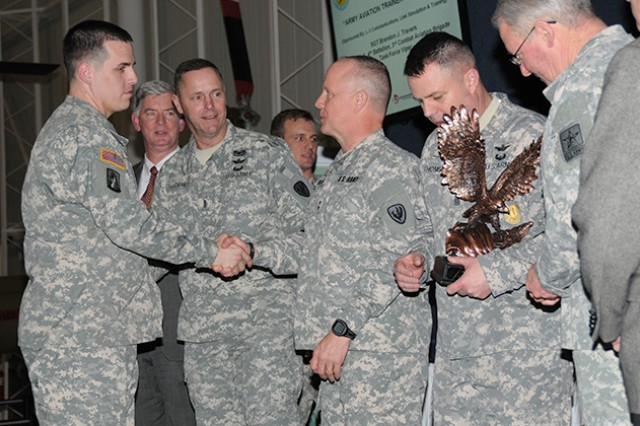 Sgt. Brandon J. Travers, A Co., 3rd CAB, TF Viper, and recipient of the 2013 Army Aviation Trainer of the Year Award, shakes hands with Maj. Gen. Kevin W. Mangum, U.S. Army Aviation Center of Excellence and Fort Rucker commanding general, during the AAAA Award Ceremony at the U.S. Army Aviation Museum Feb. 5.
