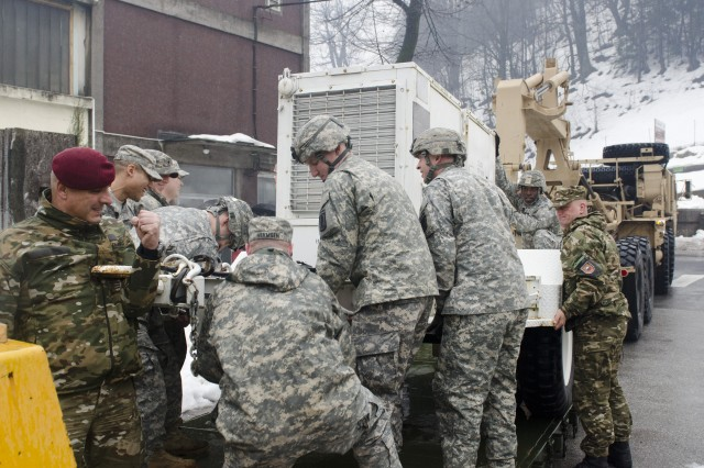 American paratroopers from the 173rd Infantry Brigade Combat Team (Airborne), and soldiers from Slovenian 1st Brigade, position a generator so that it may be unloaded during a joint convoy to deliver generators to rural villages near Postojna, Slovenia, Feb. 11, 2014.