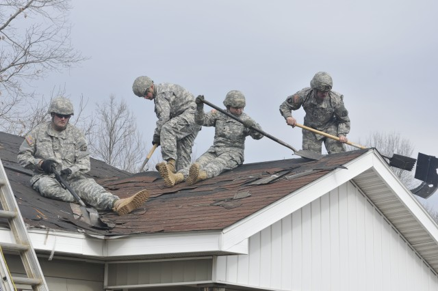 U.S. Army Reserve Soldiers from 1st Platoon, 465th Engineer Company, clear off old shingles from a damaged roof, during an Individual Readiness Training mission with Habitat for Humanity in Edgewater, Ala., Feb. 8, 2014.