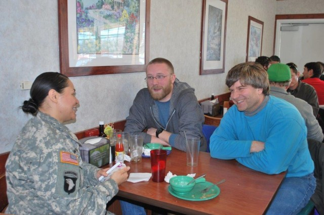 Sgt. 1st Class Michelle Williams, greening course organizer, CISD, speaks with Matthew Munson, VTD (center) and Morris Berman, WMRD (right) at a group luncheon following the UH 60 Blackhawk helicopter ride. Both Munson and Berman indicated the informal communications between the researchers and the NCOs was very valuable.