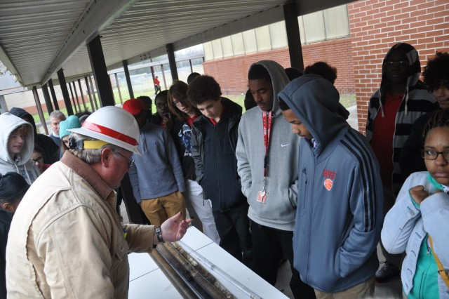 Danny Hewett, a drill rig operator with the U.S. Army Corps of Engineers Savannah District, shows students a soil sample extracted by a drill rig at Jenkins High School, Feb. 13, 2014. Members of the Corps visited Jenkins High School to promote engineering-related career paths as part of National Engineers Week.