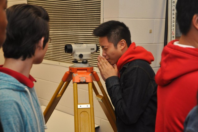 Jenkins High School students look through a surveying scope during a visit by the U.S. Army Corps of Engineers, Feb. 13, 2014. The visit aimed to recruit students to pursue science and engineering related career paths as part of National Engineers Week.