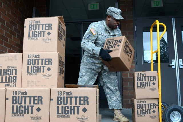 "U.S. Army Master Sgt. Nicola Silva, support operations noncommissioned officer for Headquarters and Headquarters Company, 296th Brigade Support Battalion ""Outlaws,"" 3rd Stryker Brigade Combat Team, 7th Infantry Division, Joint Base Lewis-McChord, Wash., stacks boxes of popcorn to take back to ""Frontline"" soldiers at 296th BSB. The popcorn was donated by the Boy Scouts of America and distributed by the USO Northwest. (U.S. Army photo by Staff Sgt. Justin Naylor)"