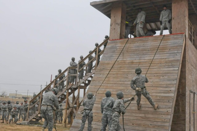 Students of the Fort Hood, Texas, Air Assault class 05-14 practice going down the slant wall, Feb. 10, 2014, before tackling the 50-foot rappel tower.  The 10-day course is designed as a crawl, walk, run course, so students can grasp the material being taught.