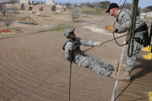 Sgt. Anthony Eashman, (left) from San Francisco, and Sgt. 1st Class Jeremy Stanton, from Midland, Texas, instructors at the Fort Hood, Texas, Air Assault School, demonstrate the proper way to rappel down the 50-foot tower, Feb. 12, 2014. The purpose of the school is to train students in air assault operations, sling-load operations and rappelling.
