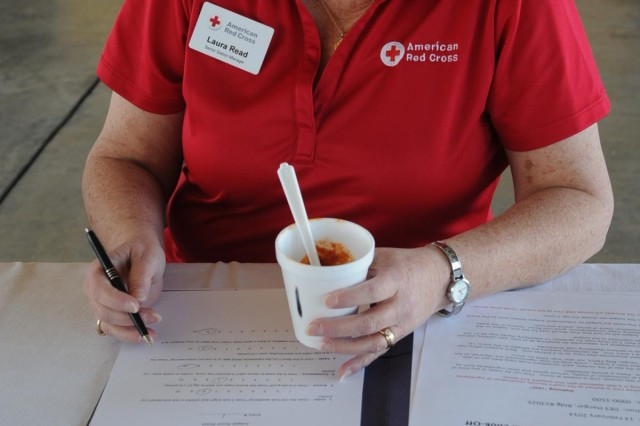 Laura Read, senior station manager with Red Cross, casts her vote of a chili entry during the 2014 Fort Hood Garrison Chili Cook-off at the Central Fire House Feb. 13. Participants in the competition looked forward to prizes and gift cards from the Red Cross, commissary, and various other organizations. (U.S. Army Photo by Sgt. Juana M. Nesbitt 13th Public Affairs Detachment)