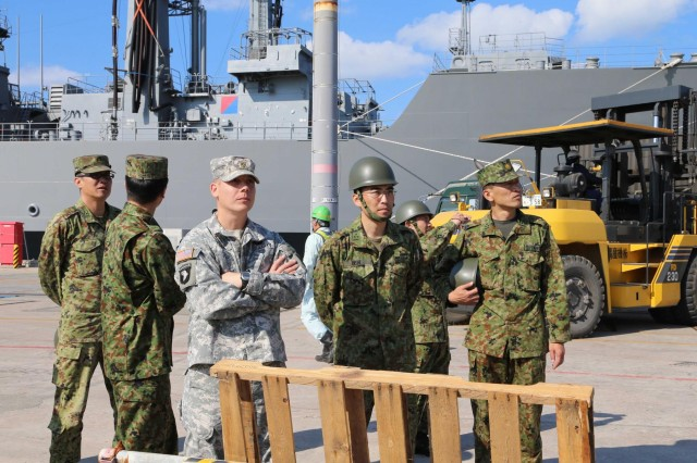 Soldiers from the Japanese Self Ground Defense Force escorted by Maj. Josh Panek, deputy support operations officer for the 10th Regional Support Group, observe port operations for exercise Pacific Utilities and Logistics Support Enablers - Watercraft Jan. 24 at White Beach Naval Base, Okinawa, Japan. The 10th RSG enhanced bilateral relations by providing insight into the mission and complexities of loading equipment and supplies onto U.S. Army watercraft.