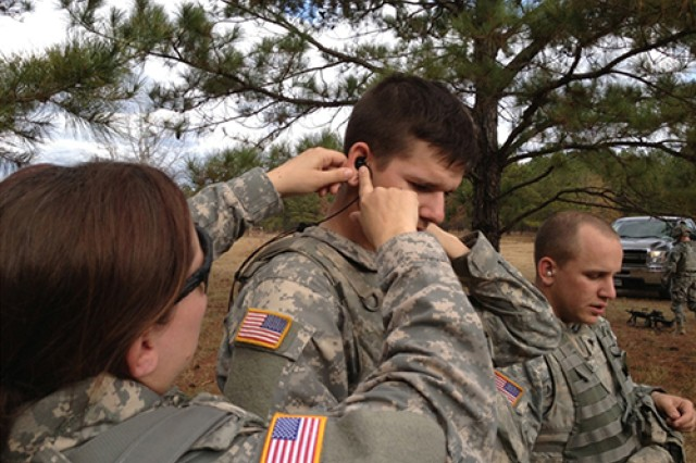 Capt. Jennifer Noetzel, chief of the Fort Drum Hearing Program, Preventive Medicine Department, fits an in-the ear TCAPS system for Pfc. Mark Epling, a member of 1st Battalion, 87th Infantry Regiment, 1st Brigade Combat Team, during hearing equipment testing in December 2012 at Fort Benning, Ga.
