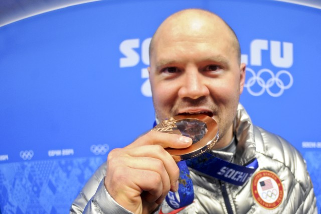 Steven Holcomb, former U.S. Army World Class Athlete Program soldier, bites his Olympic bronze medal for two-man bobsleigh at Olympic Park in Sochi, Russia, Feb. 18, 2014. Holcomb teamed with Steve Langton to claim Team USAs first medal in the event since the 1952 Olympic Winter Games in Oslo, Norway.