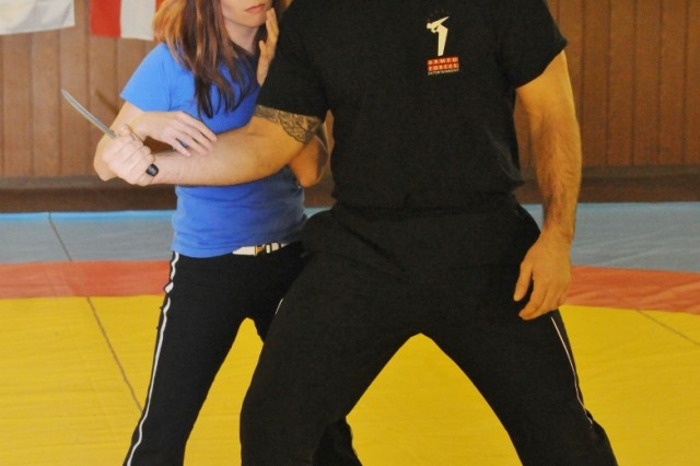 Self-defense expert Linda Vu demonstrates a technique against a knife-wielding attacker with the aid of instructor Shawn Fitzsimmons during her self-defense seminar in Hohenfels, Feb. 13..