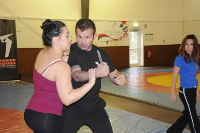 Linda Vu (right) inspects Jaclyn Martinez's knife blocking technique against instructor Shawn Fitzsimmons during the self-defense seminar in Hohenfels, Feb. 13.