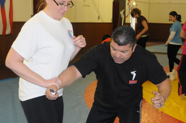 Jennifer Strahan blocks a mock attack from instructor Rick Klein during Linda Vu's self-defense seminar in Hohenfels, Feb. 13.