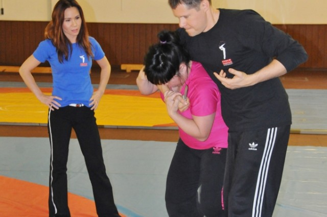 Sayoko Patterson practices escaping from a choke hold by instructor Damon Canady as Linda Vu (left) looks on during her self-defense seminar in Hohenfels, Feb. 13.