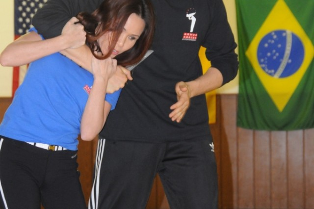 Linda Vu demonstrates how to escape from a choke hold with help from instructor Damon Canady during her self-defense seminar in Hohenfels, Feb. 13.