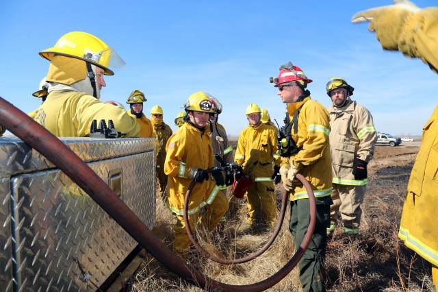 Fort Sill Fire and Emergency Services firefighter Jay Young (wearing red helmet) explains how a brush truck is used to fight wildland fires Feb. 16, 2014, at East Range here. Fort Sill supported the regional firefighting training with instructors, equipment, training facilities and land useage for the state-sponsored training.