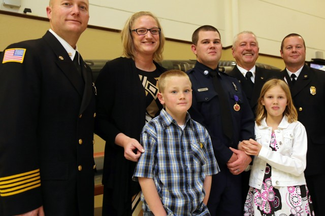 Firefighter Patrick Denton (third from left) stands with his family and leaders from Fort Sill Fire and Emergency Services after he was presented with the Fire Service Purple Heart award Feb. 14, 2014, during the opening of the Destry Horton Wildland Fire and EMS Regional School at Snow Hall. Denton was severely injured May 8, by unexploded ordnance while fighting a fire in a safety zone at West Range. Surrounding Denton from left are Chief Clint Langford, Stephanie Denton, Asst. Chief Ronald Pyle and Asst. Chief Jeremy Thomas. In front are the Denton children Payton, 8, and Jazmyne, 10.