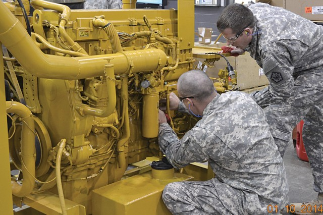 Warrant Officers Ryan Chaney and Michael Cook, 915A WOBC Class 14-02, check an electrical connection on a Caterpillar diesel engine during the engine performance training.