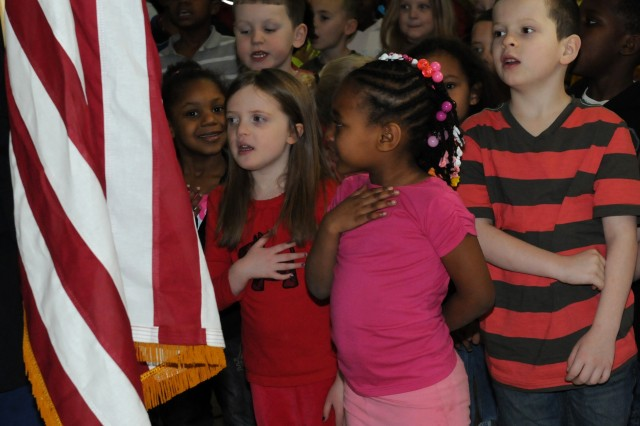 Wilson Elementary students cover their hearts and sing the national anthem as the American flag is brought forward before a rally where Army Sustainment Command Sgt. Audie Murphy Club member, Sgt. 1st Class Darrick Dupree, spoke to them at the school in Davenport, Iowa, Feb. 14. (Photo by Sgt. 1st Class Shannon Wright, ASC Public Affairs)
