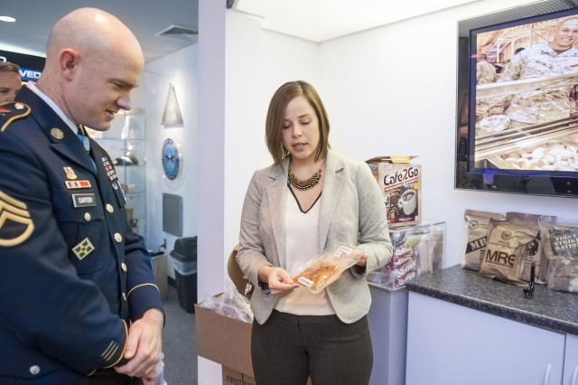 Medal of Honor recipient Staff Sgt. Ty Carter looks on as Kristina Howard, a NSRDEC food technologist, shows him a prototype of a new shelf stable pizza product developed for use in the MRE combat ration.