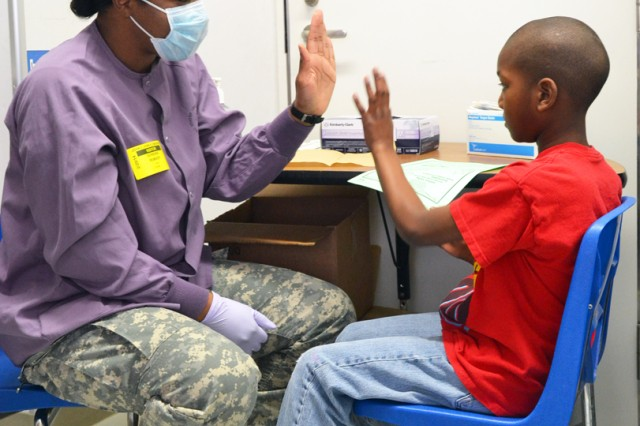 Arnn Elementary fourth-grader Khalil Foxx gives DENTAC-Japan dentist, Capt. Adrienne Rembert, DDS a high-five after an oral dental screening conducted Feb. 20, during a preventative health visit for National Children's Dental Awareness Month. (U.S. Army photos by Candateshia Pafford)