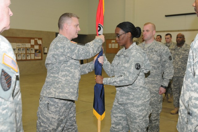 Sgt. Maj.  Jo Ann Goodwin, 1st Brigade, 94th Training Division operations & plans senior noncommissioned officer, substituting for Command Sgt. Maj. Nickolette Yungandreas, the brigade senior enlisted advisor, accepts the brigade colors from Col. Timothy D. Dye, the new brigade commander during the brigade Change of Command Ceremony where Dye succeeded Lt. Col. (P) Michael L. Bland. The ceremony took place at the brigade headquarters in Charleston, W. Va., Feb. 22, 2014.
