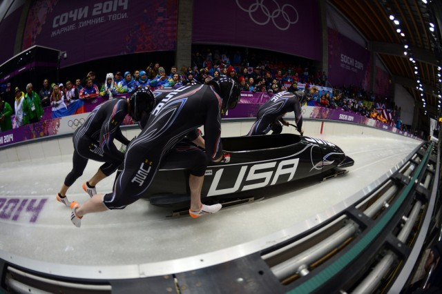 Former U.S. Army World Class Athlete Program and reigning Olympic four-man champion bobsled driver Steven Holcomb (far right) and WCAP brakeman Capt. Chris Fogt (far left), along with USA-1 crew members Steve Langton and Curt Tomasevicz, start their first heat of Olympic four-man bobsled competition Feb. 22, 2014, at Sanki Sliding Centre in Krasnaya Polyana, Russia. The USA-1 quartet is in third place after one of four heats. Russia-1, driven by Alexander Zubkov, leads with a first-run time of 54.82 seconds, followed by Germany-1, driven by Maximilian Arndt, with a time of 54.88. USA-1 posted a first-heat time of 54.89.