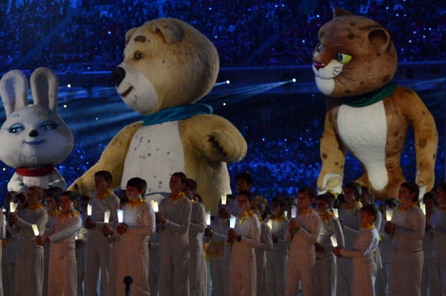 Even though the Olympic torch outside the stadium has been extinguished, Russian children safeguard their flames as the Sochi 2014 bear, hare and leopard mascots wave goodbye to the audience during the Closing Ceremony of the Winter Games in Fisht Olympic Stadium, Feb. 23, 2014, in Sochi, Russia.