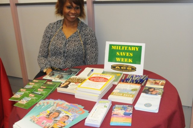 Donna Gotel, Financial Readiness Program manager, offers financial education books for lucky prize winners during Military Saves Week's kick-off party at Hohenfels, Feb. 24.