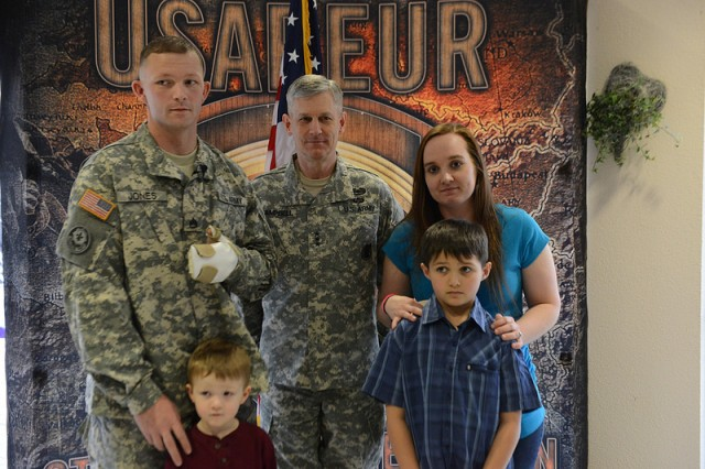 Staff Sgt. Tyronne Jones (left) with Headquarters and Headquarters Troop, 2d Cavalry Regiment, and his family pose for a photograph with Lt. Gen. Donald M. Campbell Jr. (middle), commanding general of U.S. Army Europe, Feb. 19, 2013, at Landstuhl, Germany. Jones re-enlisted during his recovery from injuries sustained during an insurgent attack in southern Afghanistan.