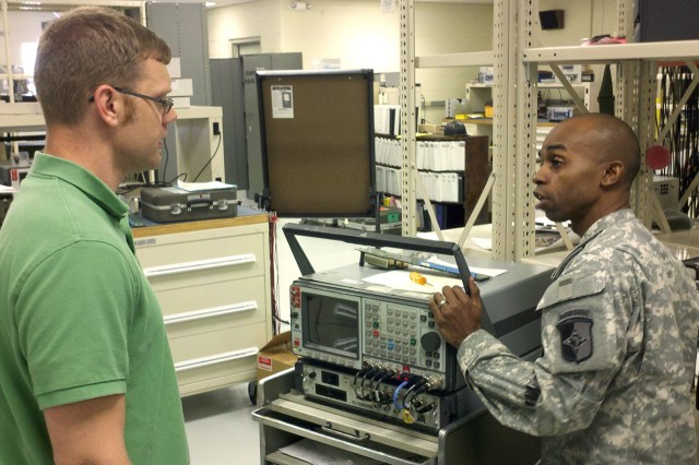 An area test, measurement, and diagnostic equipment (TMDE) support team noncommissioned officer-in-charge discusses calibration procedures for the GRM-122 radio test set with a TMDE Utilization Study representative.