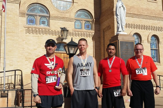 (From left to right) Maj. Erik Dye, executive officer of 3rd Battalion, 360th Regiment, Task Force Rough Rider, 5th Armored Brigade, and Observer-Coach/Trainers Sgt. Nicholas Savas, Sgt. 1st Class Jesse Galvan, and Master Sgt. Bret Sieverts, pose for a snapshot after completing the inaugural Race for Care 5K in Las Cruces, N.M., Feb. 16. Dye walked off with an overall first place trophy in the race and the other Rough Rider runners received medals in their respective age groups.