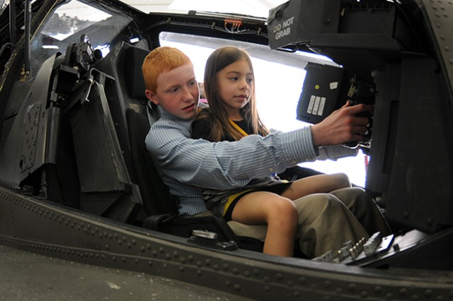 """Michael Defrenn �"""" son of CW2 Jason Defrenn, whose name now adorns the new AH-64 maintenance hangar at Hanchey Army Heliport along with CW4 Keith Yoakum �"""" sits with his cousin, AJ Still, in the cockpit of an Apache after the dedication ceremony to honor his father and Yoakum Feb. 20."""