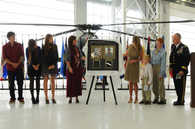 Kelly Yoakum, Jennifer Defrenn and their Families unveil a portrait of their husbands, CW4 Keith Yoakum and CW2 Jason Defrenn, during a the AH-64 Maintenance Hangar Dedication Ceremony Feb. 20. The hangar will now be known as the Yoakum-Defrenn Hangar in honor of the two men who were killed in action when their Apache was shot down in Iraq in 2007.