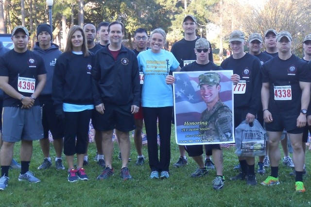FORT CAMPBELL, Ky-U.S. Army 2nd Lt. Justin Sisson�'s parents, Phyllis and Kevin Sisson, Signe Thomas, the race organizer, and Currahees with 1st Battalion, 506th Infantry Regiment, 4th Brigade Combat Team, 101st Airborne Division (Air Assault), pose for a photo the day of the first 2nd Lt. Justin Sisson Memorial 5K Race, Feb. 22, 2014, held at the Florida State University in Tallahassee, Fla.