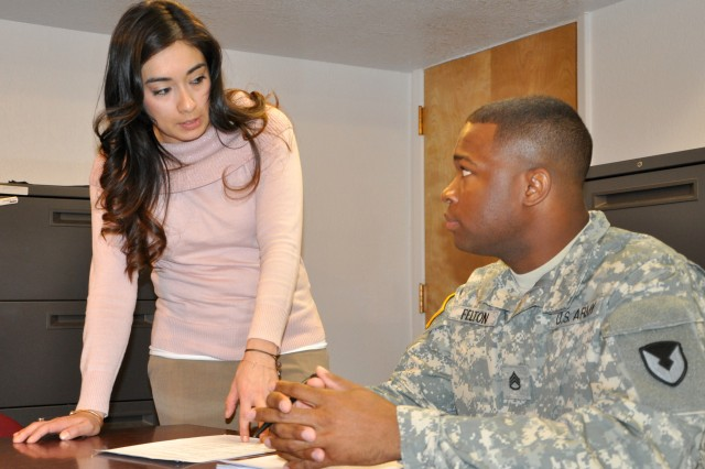 Melissa Garcia and Staff Sgt. Elijah Felton discuss a contract at Fort Bliss, Texas.  Garcia is a contracting officer and Felton is a contracting specialist at the Mission and Installation Contracting Command-Fort Bliss office.