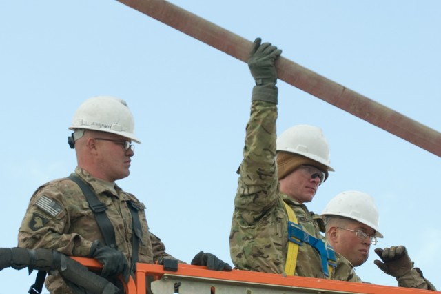 (From left) Sgt. Chris Sexton, a heavy equipment operator, Spc. Zachariah Buckner, a plumber and Sgt. Aaron Duford, an election with the 1151st Engineering Company, Alabama National Guard, 82nd Sustainment Brigade, 1st Theater Sustainment Command, pulls cut beams from a building at Bagram Airfield, Afghanistan, Feb. 3, 2014.