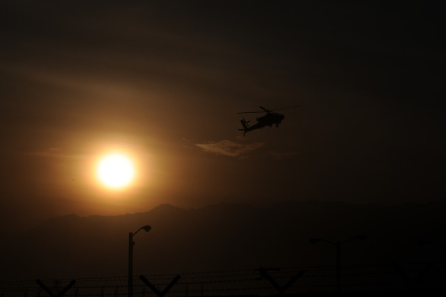 An Apache Gunship from 1st Calvary Division conducts route recon near Bagram Air Field, Afghanistan, as the sun sets over the Hindu Kush Mountain Range.