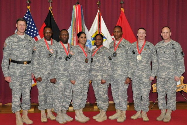 New members of the Sergeant Morales Club stand with Maj. Gen. John R. O'Connor and Command Sgt. Maj. Rodney J. Rhoades, the commanding general and the command sergeant major of the 21st Theater Sustainment Command, during an induction ceremony at the Kaiserslautern Community Activity Center on Daenner Kaserne Feb. 26.  The Sergeant Morales Club is an exclusive organization where members exemplify a special kind of leadership characterized by a personal concern for the needs, training, development and welfare of Soldiers.
