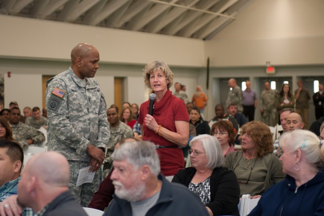 Fort Leonard Wood employee Alice Bischoff asks a question as Maj. Gen. Leslie Smith, Maneuver Support Center of Excellence and Fort Leonard Wood commanding general, looks on during the town hall meeting Feb. 19 in Nutter Field House.