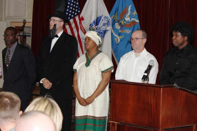 From left, Sgt. 1st Class Andre Clovis as Malcolm X; Staff Sgt. Ken Coffey as Abraham Lincoln; Staff Sgt. Michelle Taitt portraying a slave; Staff Sgt. William Condon as President John F. Kennedy; and Sgt. Maj. Lavander Wilkerson as James Brown stand before the audience after their presentations in a skit depicting highlights in the Civil Rights Movement. Not shown are Sgt. Stephen Harbison portraying Dr. Martin Luther King Jr.; Staff Sgt. Yolanda Wright as Rosa Parks; and Staff Sgt. Elissa Holtry as Harriet Tubman. These Soldiers were also part of the skit.